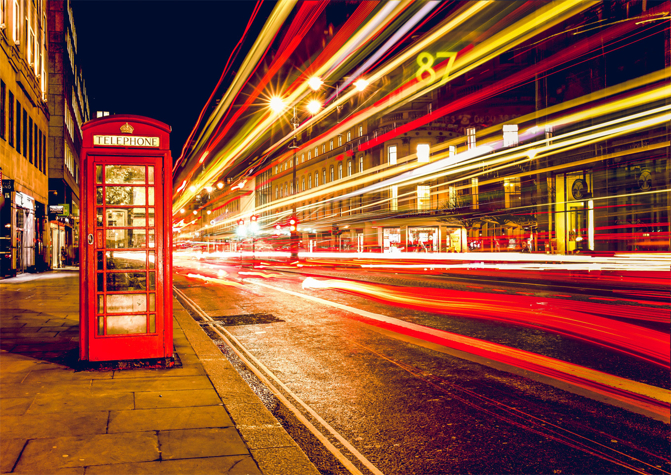 Admin Hacks: A picture of a London street. A phone box to the left and red, white and yellow lines to the right demonstrating fast moving traffic.